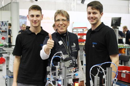 Sybille Bohland mit den Mechatronikern Felix Alt (links) und Jan Kintzi bei der Deutschen Meisterschaft auf der didacta 2019.